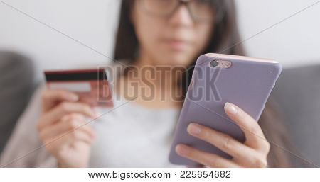 Woman shopping online with cellphone and credit card