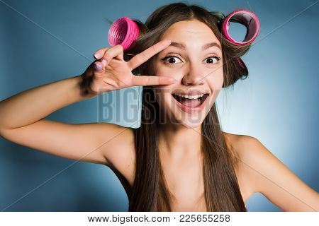 Happy Funny Girl Showing Two Fingers On A Hair Curler Head