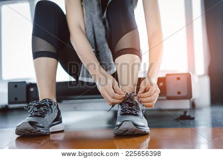Woman Knelt Down To Do Up His Shoelaces With Protein Shake At Fitness Gym After Running Exercise Wor