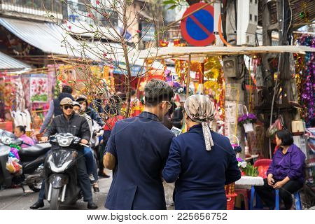 Hanoi, Vietnam - Jan 26, 2017: A Mother And Her Son Take A Walk Buying Decoration And Flower For Vie