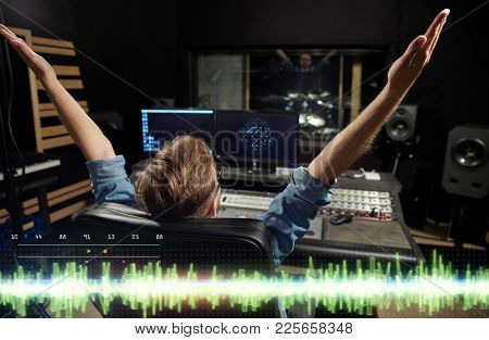 music, technology, people and equipment concept - happy man at mixing console in sound recording studio