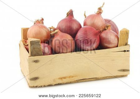 Pink onions in a wooden crate on a white background