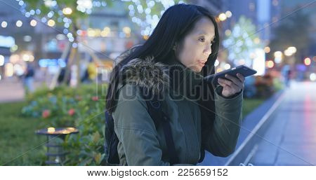 Woman sending audio message on cellphone at night