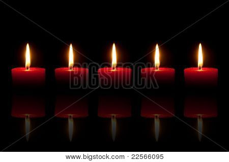 Five Burning Red Candles In Front Of Black Background