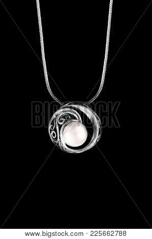 Elegant Pearl Pendant Hanging On Silver Chain Isolated Over Black