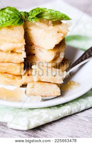 Stack Of Potato Pancakes Or Fritters With Apple Sauce And Fresh Basil Leaves On A Plate, Selective F