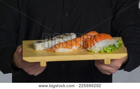 Cook hold assorted sushi food on wood dish.