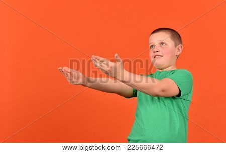 The Boy Stretches His Hands. A Good Mood. The Boy Is On An Orange Background.
