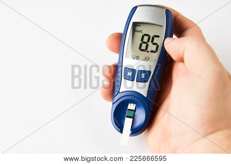 Man Checking Blood Sugar Level With Glucometer Or Blood Glucose Meter And Test Stripe Isolated On Wh