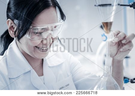 Successful Experiment. Selective Focus On A Radiant Mature Woman In Safety Glasses Grinning Broadly