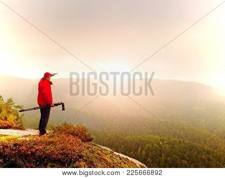 Photographer Think About Picture On Peak  In The Misty Mountains. Photograph At Daybreak Above Valle