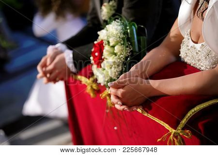 The Bride And Groom Kneeling In The Church, Only Hands