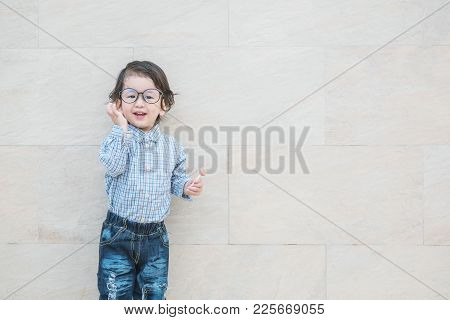 Closeup Asian Kid With Eyeglasses In Happy Motion With Candy In His Hand On Marble Stone Wall Textur