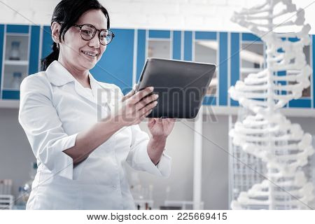 No Time For Worries. Low Angle Shot Of A Mature Lady Wearing Glasses And A Lab Coat Smiling Cheerful