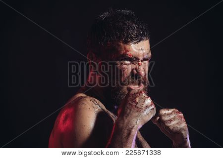 Bearded Hipster With Blood Paint On Angry Face. Man In Fight Position With Fists On Black Background