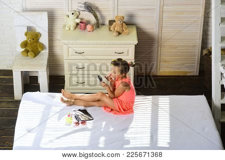 Little Girl Paints Lips With Lipstick Sitting On Bed In Childroom. Child Wears Nice Dress, Holds Mir