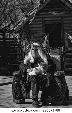 Druid Old Man With Long Grey Hair Beard With Crown In Fur Coat Holds Cat And Sits In Wooden Chair On