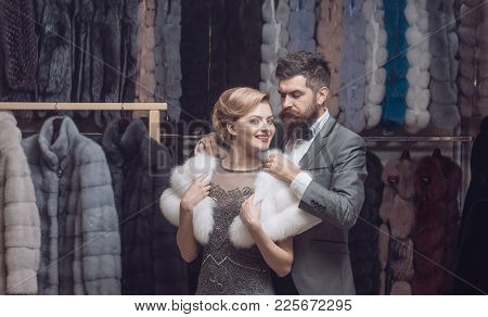 Rich Fashion Concept. Man And Girl With Happy Face Choose Furry Coats On Clothes Rack Background. Co