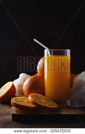 A Glass Of Orange Juice With A Pipe, A Cut Orange, Oranges On A Wooden Board, A Dark Background. Bea