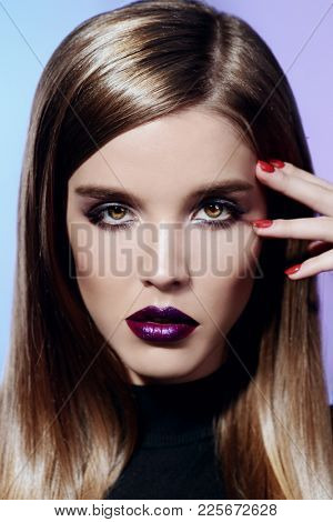 Portrait of an attractive girl with bright makeup and violet lips. Styling for long hair. Cosmetics, make-up.