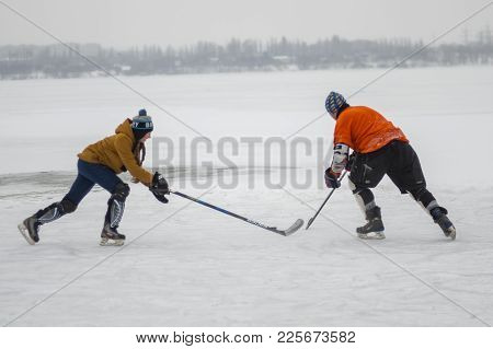 Dnipro, Ukraine - January 28, 2018: Teenager Girl Fight With Mature Man For The Puck While Playing H