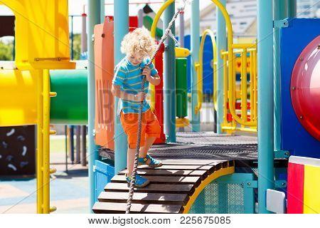 Kids On Playground. Children Play In Summer Park.