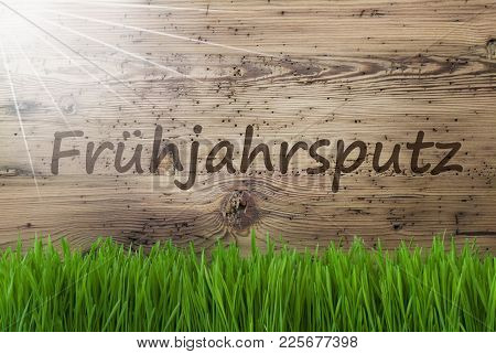 German Text Fruehjahrsputz Means Spring Cleaning. Spring Season Greeting Card. Sunny Aged Wooden Bac