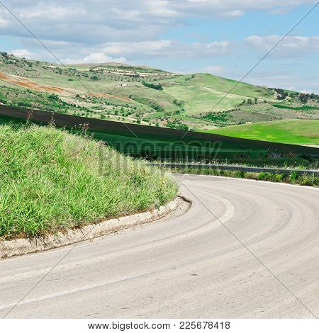 Winding Asphalt Road Between Stubble Fields Of Sicily