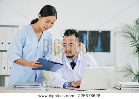 Nurse Showing Medical History To General Practitioner