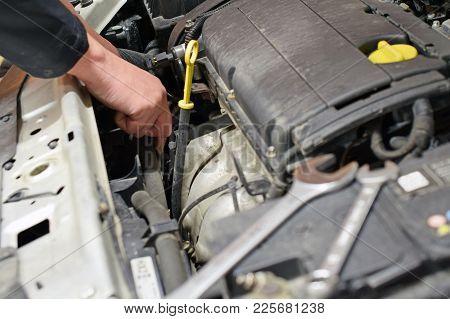 Auto Mechanic Repairs Car At Garage. Horizontal Image
