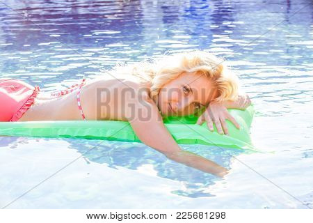 Woman Swims With Airbed At The Swimming Pool In Summer Sunlight