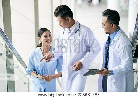 Doctor Giving Instructions To Young Interns When They Are Walking Up The Stairs