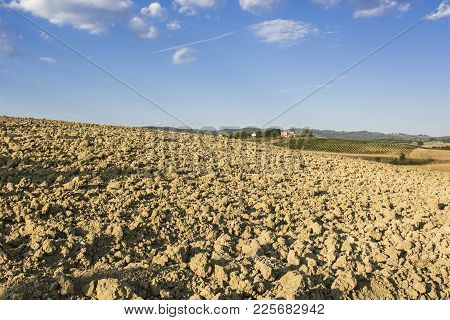 Italian Wine Farm Surrounded With Plowed Sloping Hills Of Tuscany In The Autumn. Rural Landscape Wit