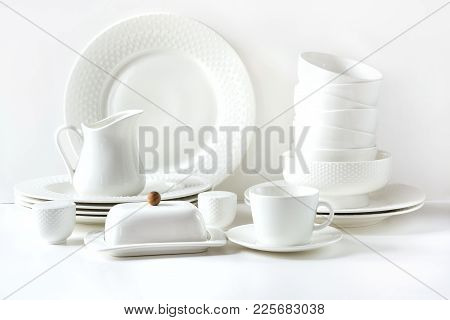 White Tableware For Serving. Crockery, Dish, Utensils And Other Different White Stuff On White Table