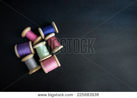 Set Of Pastel Colors Thread For Sewing On A Black Background. Set Of Threads On Bobbins Retro Style.
