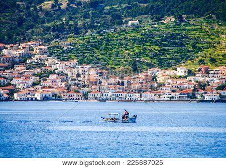 Small Fishing Boat Crossing The Blue Waters Opposite The Beautiful Island Of Spetses, Located In Sar