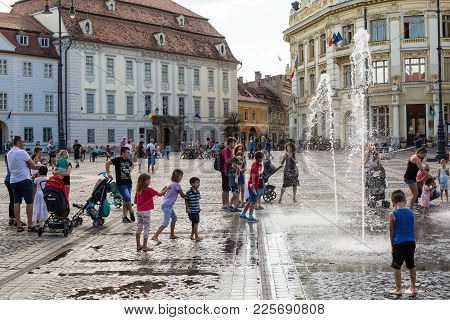 Sibiu - Romania, July 18, 2017: Child Playing With Water On Large Square In Sibiu, Romania
