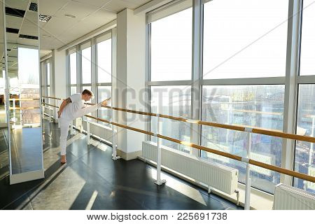 Male Dancer Doing Leg Stretching Near Window At Gym Studio. Young Person Wears White Suit. Concept O