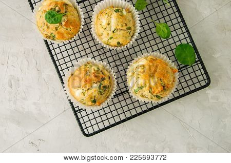 Savory Muffins With Feta Cheese And Spinach  On A Wire Rack On A White Stone Backdrop.
