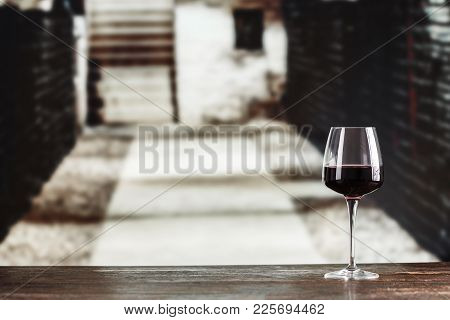 Young Wine In Glasses Against The Background Of The Cellar. In The Cellar Wine Is Located On The She