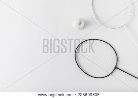 Top View Of Badminton Rackets With Suttercock On White Surface