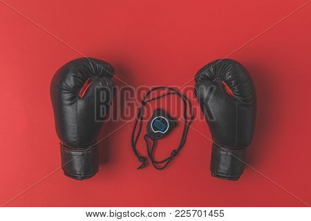 Top View Of Boxing Gloves With Stopwatch On Red Tabletop