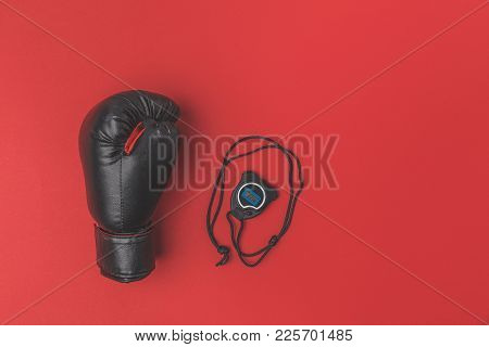 Top View Of Boxing Glove With Stopwatch On Red Tabletop