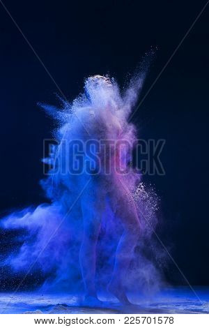 Male Nude Figure Shot Fully In A Cloud Of Blue Dust In Dark Room