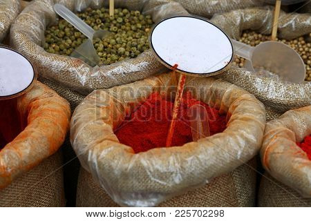 Close Up Several Canvas Bags Of Assorted Spices, Red Paprika And Green Pepper,  With Copy Space Of B