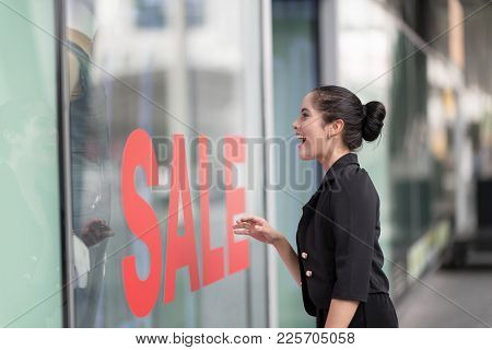 Woman Excited Looking Into Shop With Shop Window Display With Text Sale On Red Poster.going Shopping
