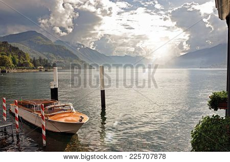Como, Italy - May 06, 2013. View Of Lake Como In A Cloudy Day With Motorboat And Harbor In Bellagio,