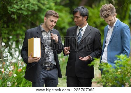 Three Of Student And Senior Professor Walk And Talk Together In The Univecity Garden.professor Consu