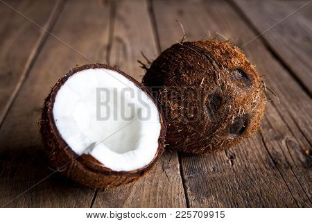 Ripe Half Cut Coconut On A Wooden Background. Ripe Half Cut Coconut On A Wooden Background. Coconut