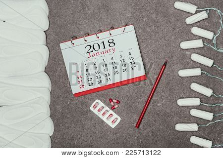 Top View Of Arranged Menstrual Pads And Tampons, Calendar And Pills On Grey Surface